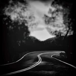 moody black and white image of a road
